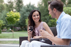 Jeunes couples heureux ayant le vin rouge sur des chaises dans le parc Photo libre de droits