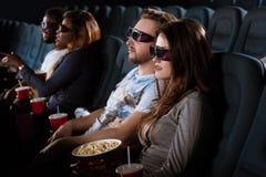 Jeunes couples heureux ayant une date au cinéma Image stock