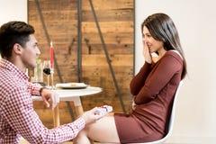 Jeunes couples heureux célébrant la proposition d'engagement image stock