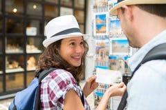 Jeunes couples heureux choisissant des cartes postales pendant des vacances images libres de droits