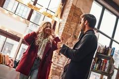 Jeunes couples heureux choisissant des chapeaux et des chapeaux au petit marché en plein air fait main photographie stock