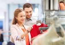 Jeunes couples heureux choisissant la robe dans le mail Image stock