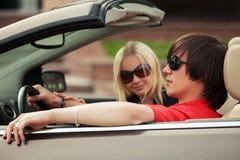 Jeunes couples heureux conduisant la voiture convertible Image stock