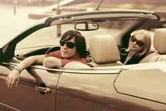 Jeunes couples heureux conduisant la voiture convertible Photo libre de droits