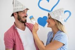 Jeunes couples heureux détendant après peinture de leur maison image libre de droits