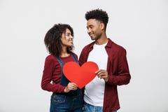 Jeunes couples heureux d'Afro-américain dans l'amour tenant le coeur de papier rouge Photographie stock