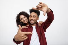 Jeunes couples heureux d'Afro-américain regardant par un cadre de doigt et souriant tout en se tenant d'isolement sur le blanc Photos stock