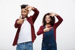 Jeunes couples heureux d'Afro-américain regardant par un cadre de doigt et souriant tout en se tenant sur le blanc Photos stock