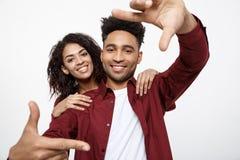 Jeunes couples heureux d'Afro-américain regardant par un cadre de doigt et souriant tout en se tenant sur le blanc Photo libre de droits