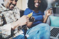 Jeunes couples heureux d'afro-américain se reposant sur le sofa à la maison et faisant des emplettes en ligne par l'ordinateur no Photo stock