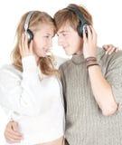 Jeunes couples heureux dans des écouteurs Photos stock