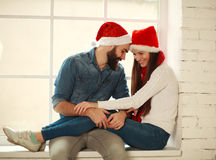 Jeunes couples heureux dans des chapeaux rouges de Noël se reposant sur la fenêtre Photo stock