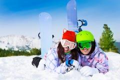 Jeunes couples heureux dans des masques de ski se trouvant ensemble Images stock