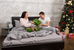 Jeunes couples heureux dans des pyjamas se donnant des présents tandis que s Photographie stock libre de droits
