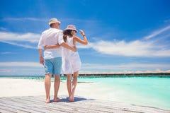 Jeunes couples heureux dans des vêtements blancs ayant l'amusement par la plage Photos libres de droits