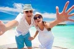 Jeunes couples heureux dans des vêtements blancs ayant l'amusement par la plage Photo libre de droits