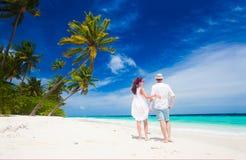 Jeunes couples heureux dans des vêtements blancs ayant l'amusement par la plage Image libre de droits
