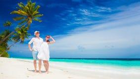Jeunes couples heureux dans des vêtements blancs ayant l'amusement par la plage Photos stock