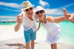 Jeunes couples heureux dans des vêtements blancs ayant l'amusement par la plage Images libres de droits
