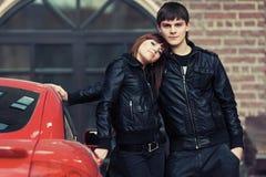 Jeunes couples heureux dans l'amour à côté de la voiture de sport Photos libres de droits