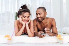 Jeunes couples heureux dans l'amour écoutant la musique avec des écouteurs Images stock