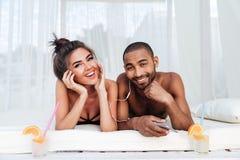 Jeunes couples heureux dans l'amour écoutant la musique avec des écouteurs Images libres de droits