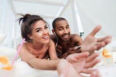 Jeunes couples heureux dans l'amour écoutant la musique avec des écouteurs Photo libre de droits