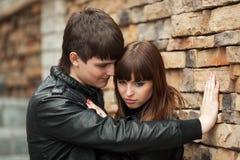Jeunes couples heureux dans l'amour au mur de briques Images stock