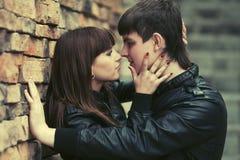 Jeunes couples heureux dans l'amour au mur de briques Image libre de droits