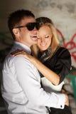 Jeunes couples heureux dans l'amour au mur sale Images stock