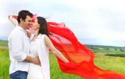 Jeunes couples heureux dans l'amour avec le tissu rouge dans le jour d'été Photos stock