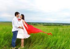Jeunes couples heureux dans l'amour avec le tissu rouge dans le jour d'été Photos libres de droits