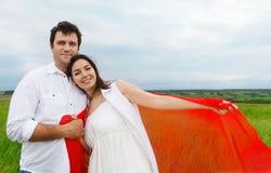 Jeunes couples heureux dans l'amour avec le tissu rouge dans le jour d'été Images libres de droits