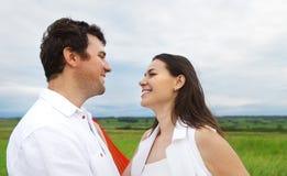 Jeunes couples heureux dans l'amour avec le tissu rouge dans le jour d'été Photographie stock