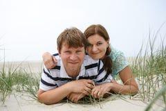Jeunes couples heureux dans l'amour ayant l'amusement sur des dunes de sable de la plage Image libre de droits