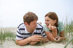 Jeunes couples heureux dans l'amour ayant l'amusement sur des dunes de sable de la plage Photo libre de droits