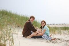 Jeunes couples heureux dans l'amour ayant l'amusement sur des dunes de sable de la plage Photos libres de droits