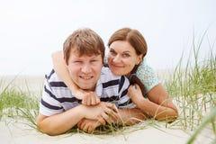 Jeunes couples heureux dans l'amour ayant l'amusement sur des dunes de sable de la plage Photo stock