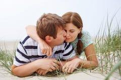 Jeunes couples heureux dans l'amour ayant l'amusement sur des dunes de sable de la plage Image stock