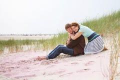 Jeunes couples heureux dans l'amour ayant l'amusement sur des dunes de sable de la plage Photographie stock