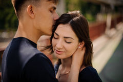 Jeunes couples heureux dans l'amour dans un moment romantique de l'homme embrassant son épouse dans le front Images libres de droits