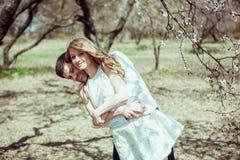 Jeunes couples heureux dans l'amour dehors homme et femme affectueux sur une promenade au parc de floraison de ressort Photos stock