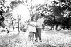 Jeunes couples heureux dans l'amour ensemble sur le coucher du soleil de paysage de parc avec le ventre enceinte de femme Photographie stock libre de droits