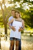 Jeunes couples heureux dans l'amour ensemble sur le coucher du soleil de paysage de parc avec le ventre enceinte de femme Images stock