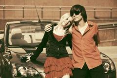 Jeunes couples heureux dans l'amour près d'une nouvelle voiture Image stock