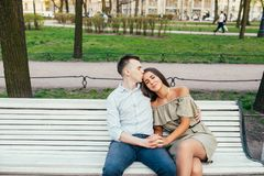 Jeunes couples heureux dans l'amour se reposant sur un banc et étreindre de parc Photo stock