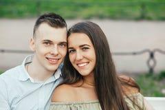 Jeunes couples heureux dans l'amour se reposant sur un banc et étreindre de parc Photo libre de droits