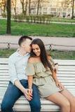Jeunes couples heureux dans l'amour se reposant sur un banc et étreindre de parc Photos stock