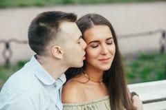 Jeunes couples heureux dans l'amour se reposant sur un banc et étreindre de parc Photographie stock libre de droits