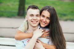 Jeunes couples heureux dans l'amour se reposant sur un banc et étreindre de parc Photographie stock